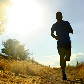 front silhouette of young sport man running on countryside in cross country workout at summer sunset with harsh sunlight effect in competition sacrifice and healthy lifestyle concept