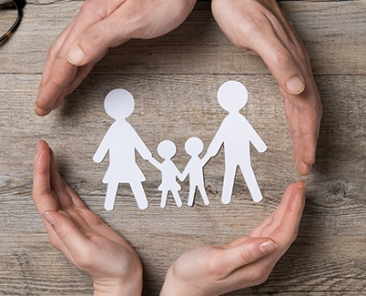 Close up of female and male hands protecting a paper chain family. Top view of two hands form a circle around white paper chain family on wooden table. Family care, insurance and helping hand concept.