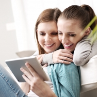 Happy lesbian couple spending time together with tablet on sofa at home. ** Note: Shallow depth of field